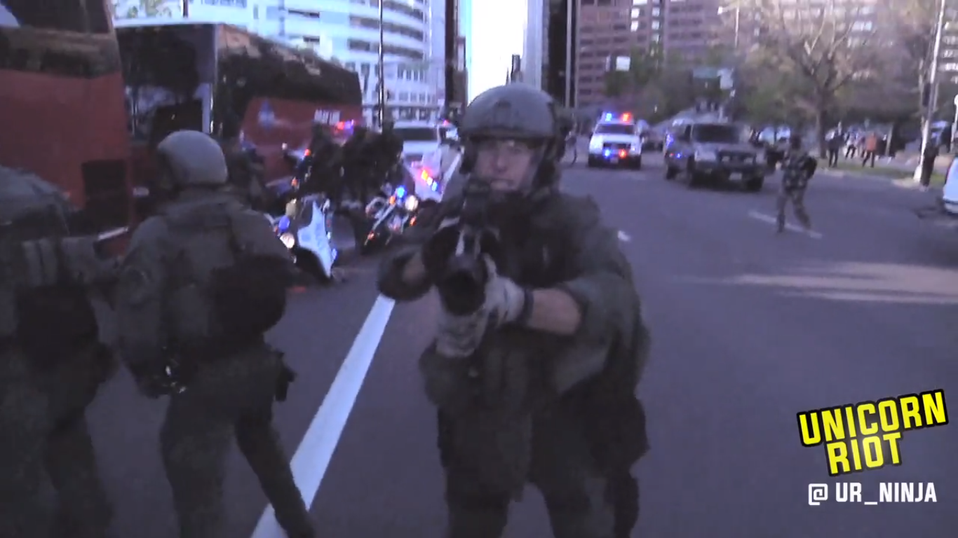 A member of DPD Metro/SWAT cocks a teargas grenade launcher at Unicorn Riot producer on April 29, 2015