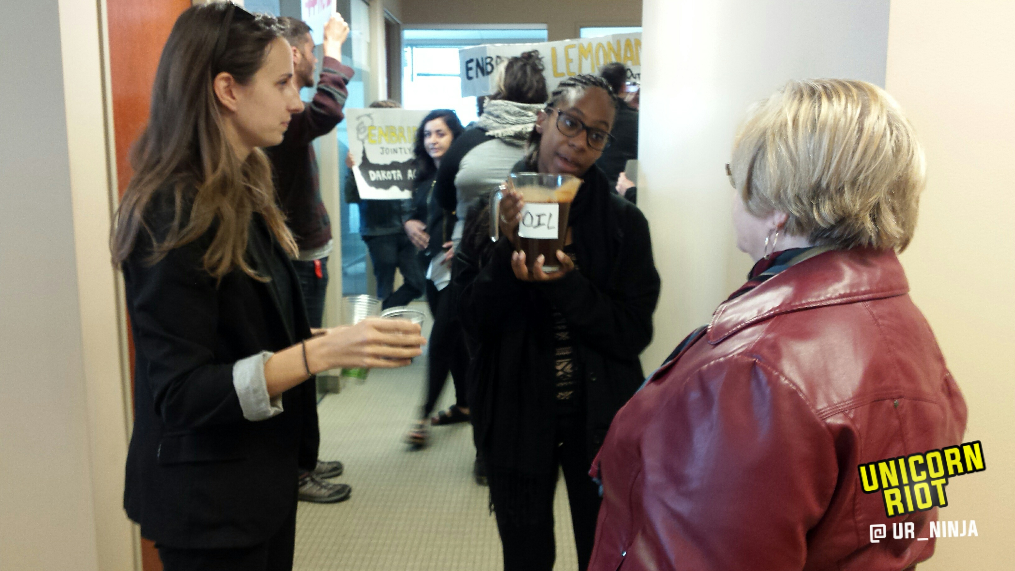 """Community members, water protectors offer cups of """"oil"""" to Enbridge employees"""
