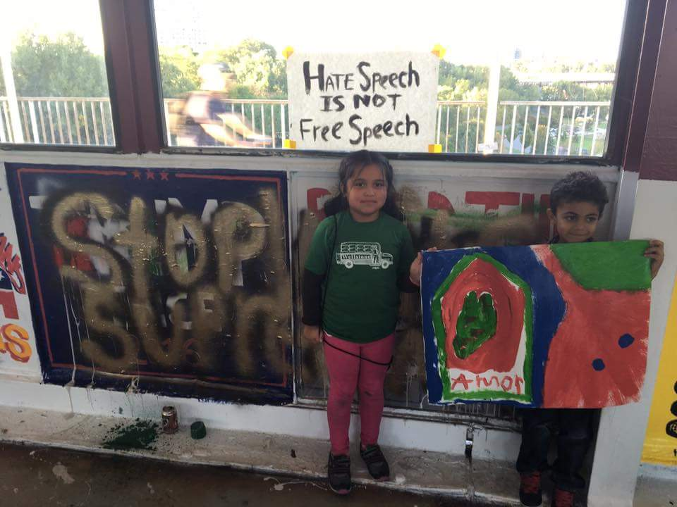 "Children in front of the mural. A sign behind reads ""Hate Speech is not Free Speech."""