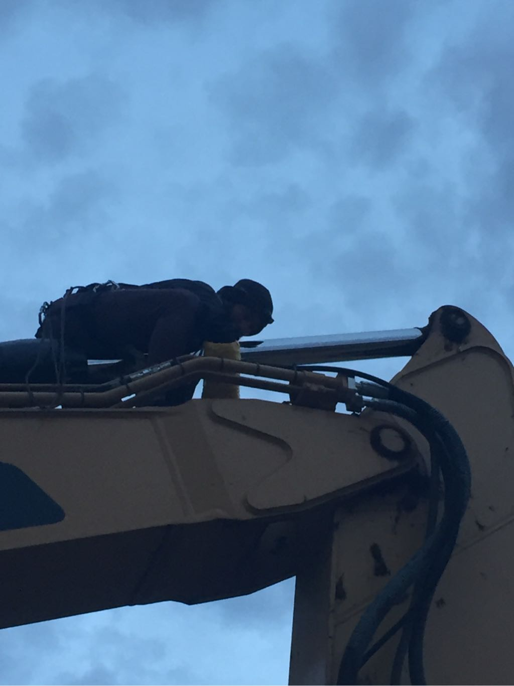 A water protector attaching themselves to the hydraulic arm of a DAPL excavator using a lockbox device