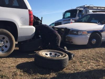 Law enforcement changing a flat tire on Highway 6. Image credit: KFYRTV