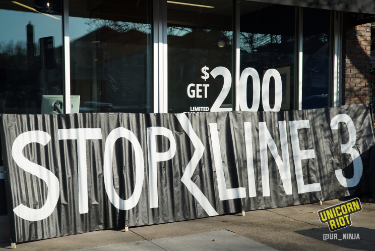 "large black banner reading ""Stop Line 3"" in white, placed alongside front of brand-new Chase Bank branch in St. Paul, MN."