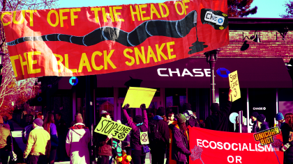 "cover image showing outside of rally at Chase Bank in St. Paul with a large banner that says ""cut off the head of the black snake"" with the ""Chase"" logo on the head of a painted black snake"