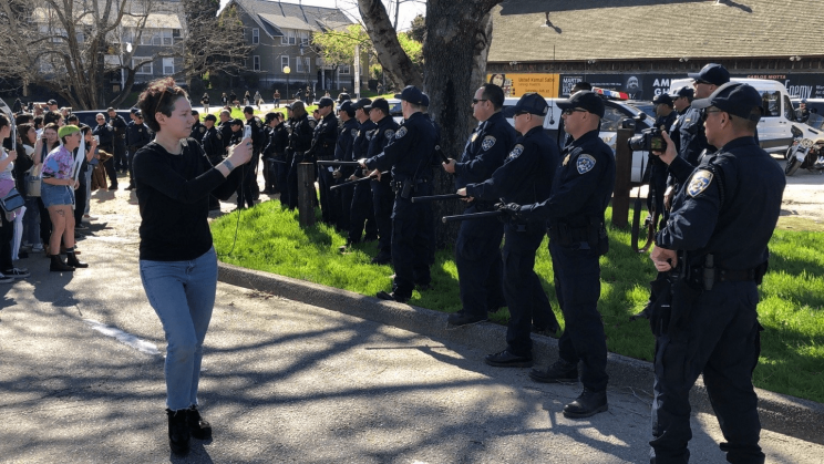 A line of dozens of riot police square off against student protesters at UCSC. Organizer Yulia Gilich stands between the students and the police, recording the police with her cell phone.