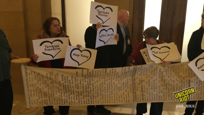 Several community members are holding up individual signs each featuring the name of a person who had been killed by the police. The community members are standing behind a long scroll of paper unrolled horizontally that lists hundreds of names of people killed by police.