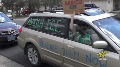 "Image description: a gold minivan is painted with the words ""Abolish I.C.E."" and ""Free Them Now"" on the windows and sides of the vehicle. A protester's arm holds a sign aloft outside the passenger window; the sign reads ""Abolish ICE"""