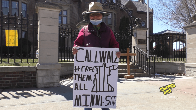 A woman smiles while holding a sign that reads, Call Walz, 'Free Them All Minnesota' with an accompanying drawing of the outline of the state of Minnesota with prison bars. She is wearing a broad-rimmed hat in the sunshine, as well as a medical face mask, which is pulled down to show her smile. She is standing in front of the Minnesota Governor's residence. In the background behind her is a wooden cross, adorned with a crucifix and the initialism INRI, placed at the entrance to the governor's residence.