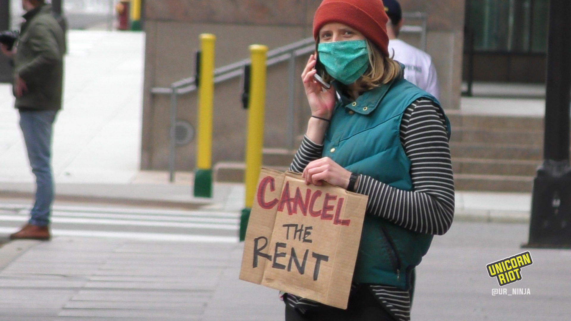 "Masked person on the phone holds ""cancel the rent"" sign"