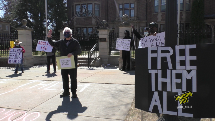 image: a demonstrator with white hair waves his right hand while holding a sign in his left hand that reads 'Free Them All.' He is wearing a face mask made from dark-colored cloth and is standing in front of the governor's residence in Saint Paul. In the foreground is a sign that also reads 'Free Them All' in white text on a black background.