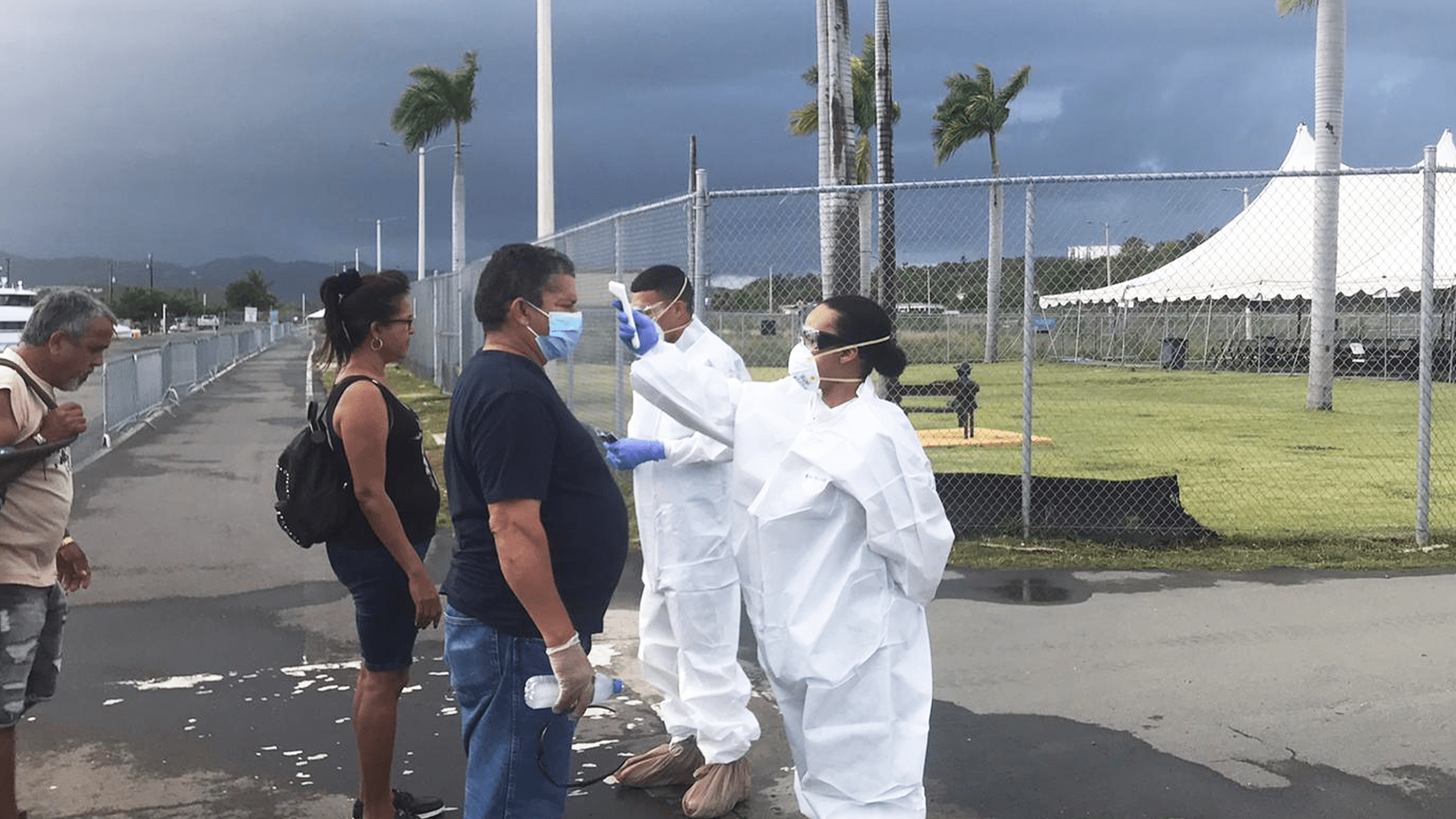 Image: members of the Puerto Rican National Guard wearing masks, eye protection, and white dust suits screen recently-deboarded passengers from an airplane before permitting them to enter Puerto Rico.