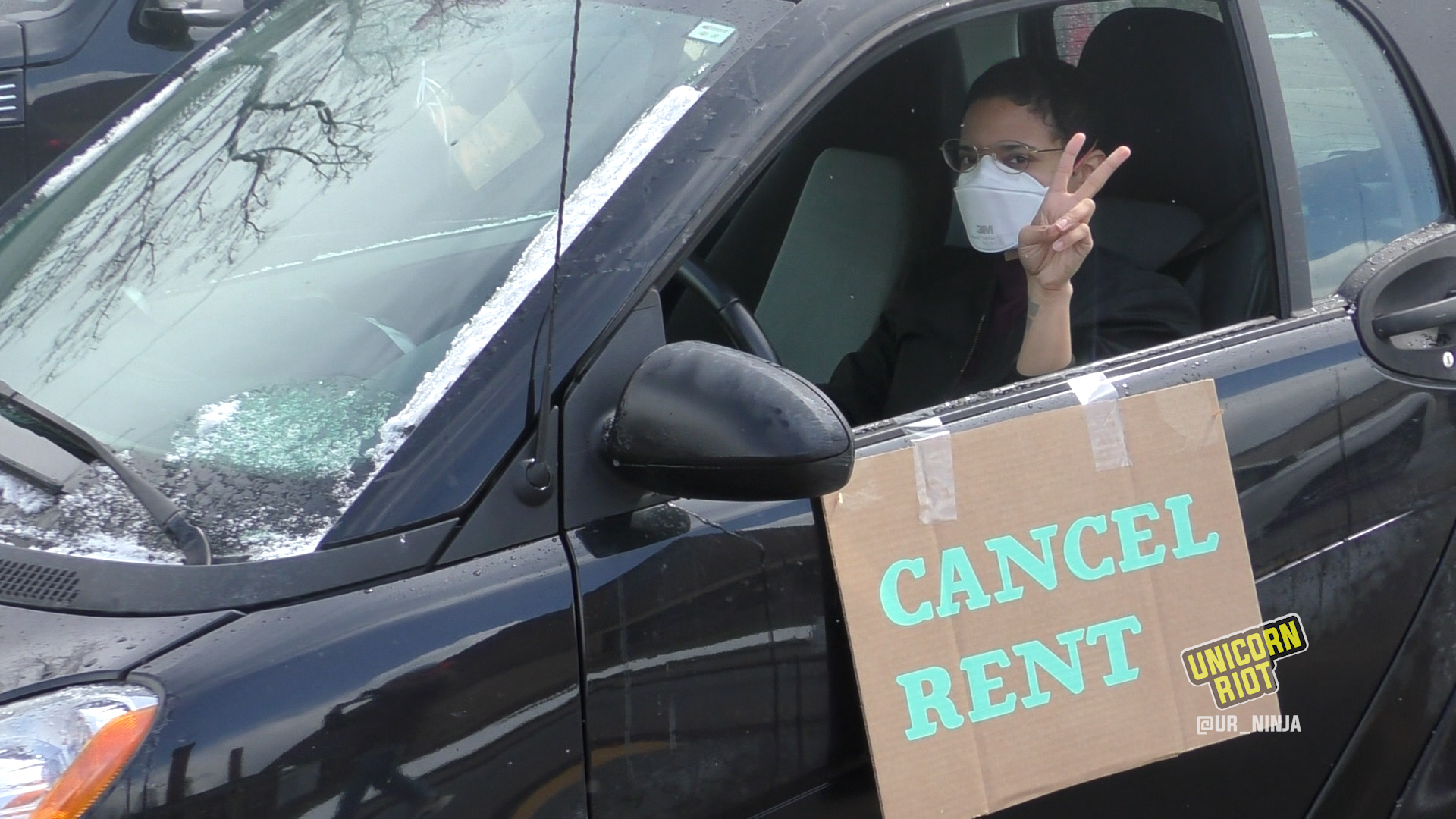 "a peace sign is shown by a person with a ""cancel rent"" sign on their car"
