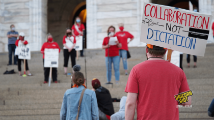 "image: a protester holds a sign, ""Collaboration - Not - Dictation. #DoBetter"" They are wearing a red t-shirt and are wearing an orange-and-black baseball cap. In the background are protesters standing ~6' apart on the steps of the Capitol building in Saint Paul."