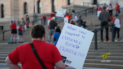 "image: a protester stands facing away from the camera, holding a sign, ""What ever happened to EVIDENCE BASED PRACTICE???"" They are wearing a red t-shirt and a black bag with a black strap slung diagonally over their shoulders. In the background are protesters standing ~6' apart on the steps of the Capitol building in Saint Paul."