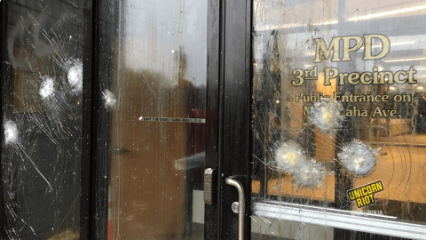 Image: the side entrance to the Minneapolis Police Department uses bullet-proof glass in the windows and door, which are each showing several fractures from having objects thrown at them from protesters. 'MPD 3rd Precinct, Public Entrance on Minnehaha Ave.' is written in gold stencils on the door.