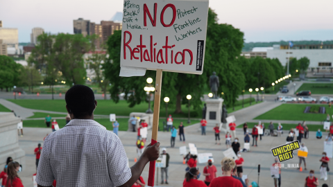 """image: a protester stands in front of the entrance to the Minnesota state capitol facing the crowd of protesters, who are spaced out physically-distanced from one another by small orange cones. The protester is holding a sign, """"NO retaliation, #BringBackCliffAndMonica, Protect Frontline Workers"""""""
