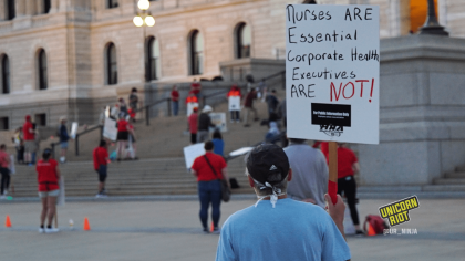 "image: a protester stands facing away from the camera, holding a sign: Nurses are essential, corporate executives ARE NOT."" The person is wearing a dark blue baseball cap and a light blue t-shirt."