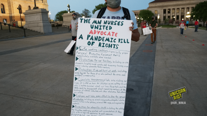 "image: a protester holds a handmade long sign, ""The MN Nurses United Advocate a Pandemic Bill of Rights"" listing the first six points on the document."