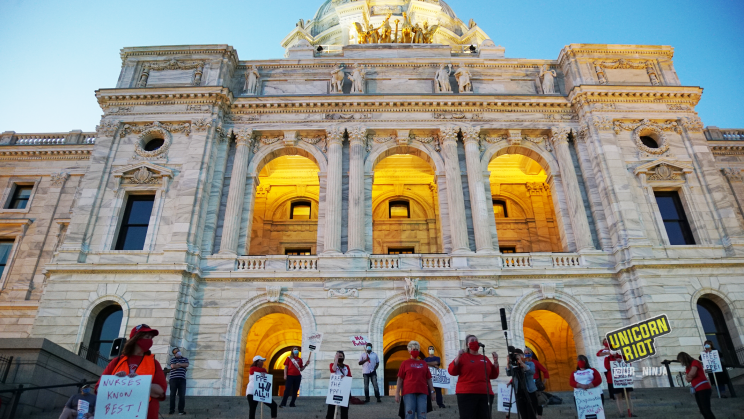 image: protesters stand on the steps in front of the entrance to the Minnesota Capitol building. The sun is setting and as the sky grew darker the lights on the grounds turned on, including the building itself which is backlit with an orange/yellow glow behind the people.