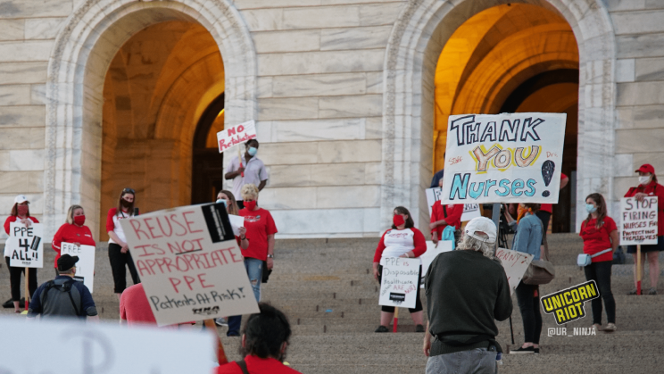 "Image: two signs held by two different protesters (both of whom are facing away from the camera): first, in the foreground on the left, ""Reuse is NOT Appropriate PPE;"" secondly, behind it on the right, ""Thank You Nurses!"""