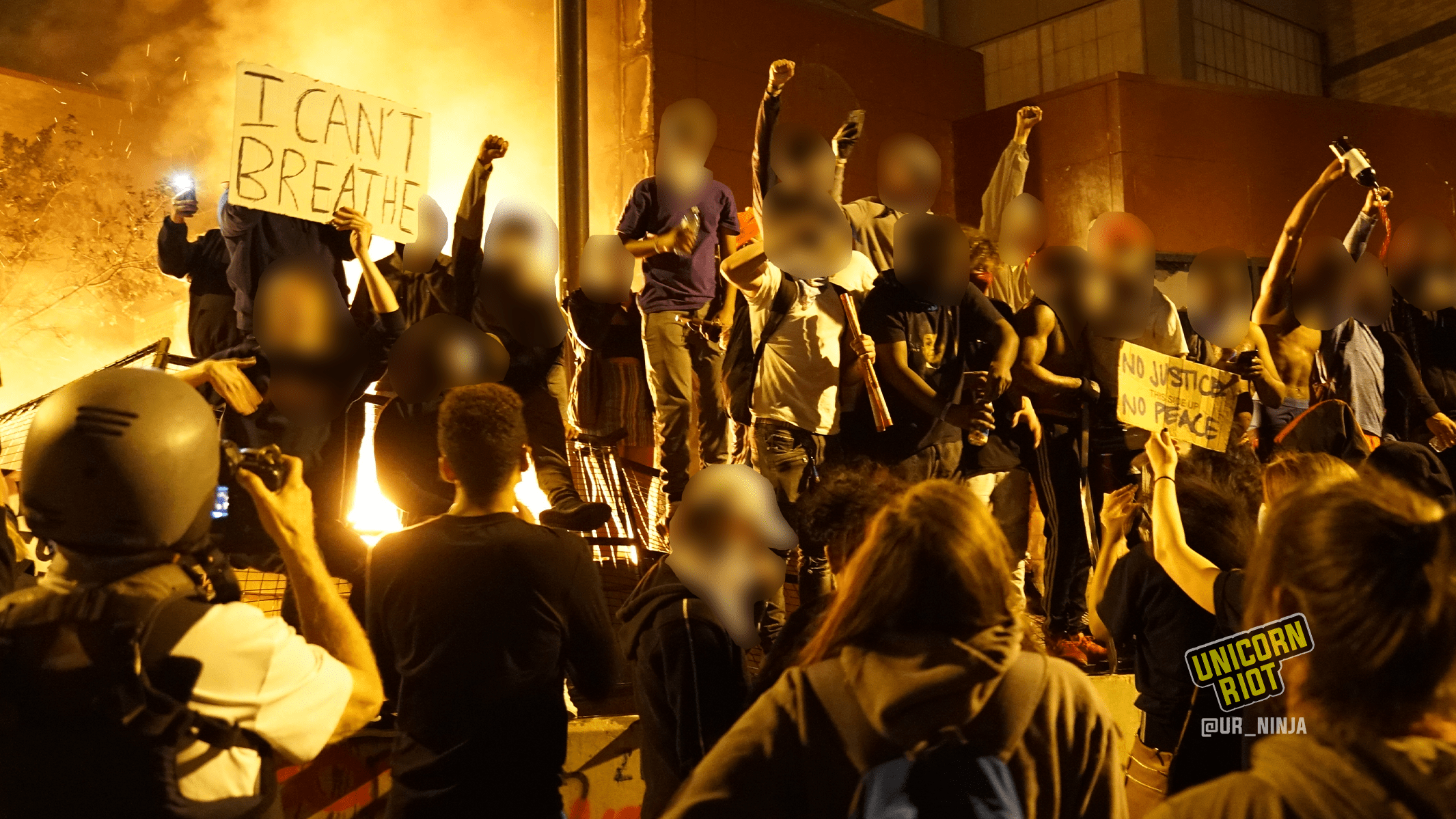 image: dozens of protesters raise their fists as first burn behind them on the grounds of the 3rd precinct. Photo taken at midnight on May 29, 2020