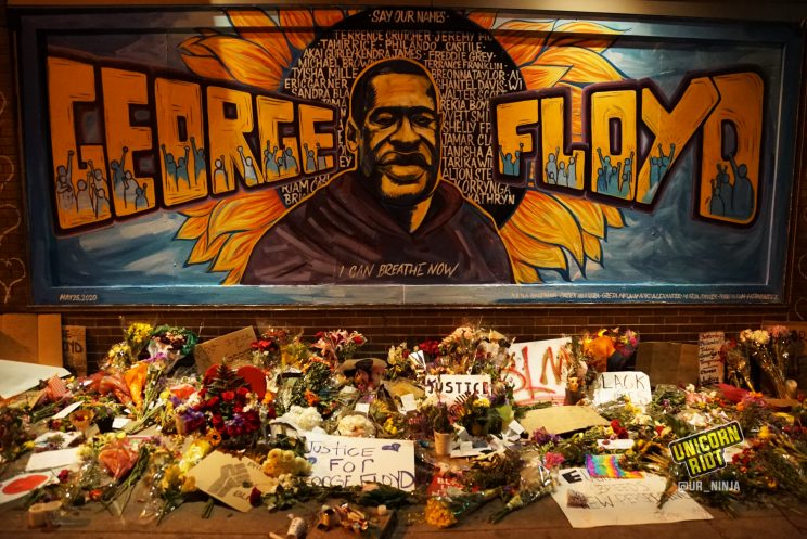 image: photo of large George Floyd mural shows a portrait of Floyd, with his name George on the left and Floyd on the right of his image. A huge sunflower is behind all of this. Painted in the center of the sunflower are many other names lost to police violence.