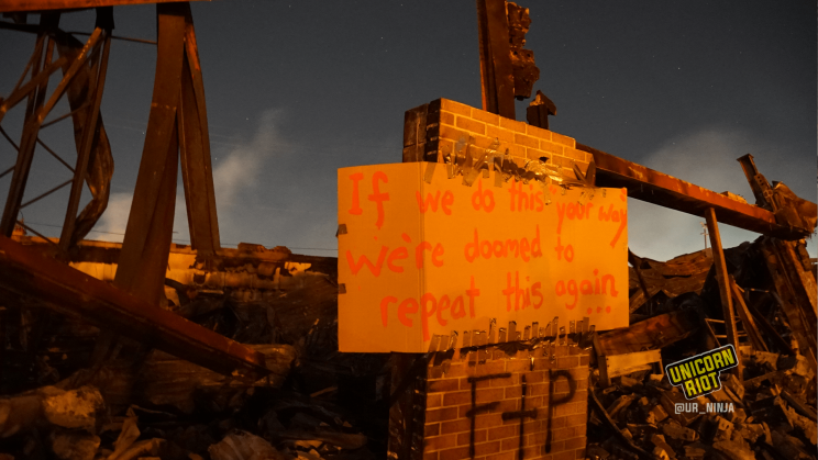 "image: a protest sign has been affixed to a tower of bricks still standing amidst the burned rubble of the AutoZone: ""If we do this 'your way' we're doomed to repeat this again..."" Behind the remains of the building, stars are visible in the night sky."