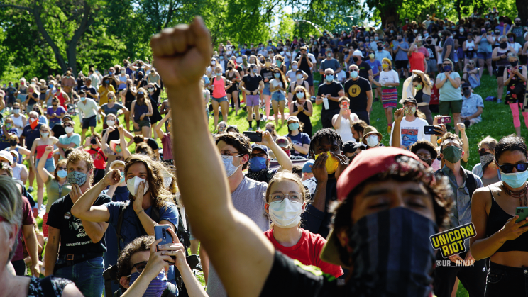 image: the hill of protesters reacts positively to the notion of defunding & disbanding the Minneapolis police department. One person in the foreground has their right arm raised over their head making a closed fist.