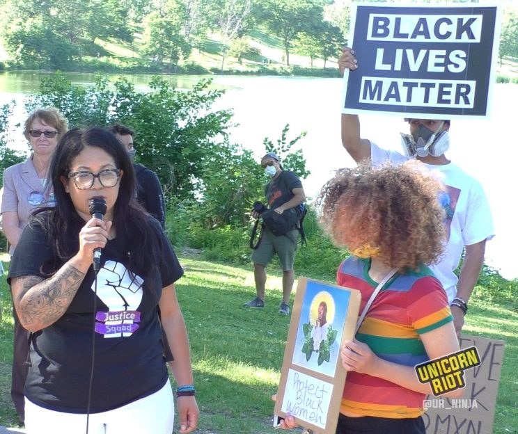 Ashley Quinones speaks while woman holds sign with Oluwatoyin Salau's image and Protect Black Women in words
