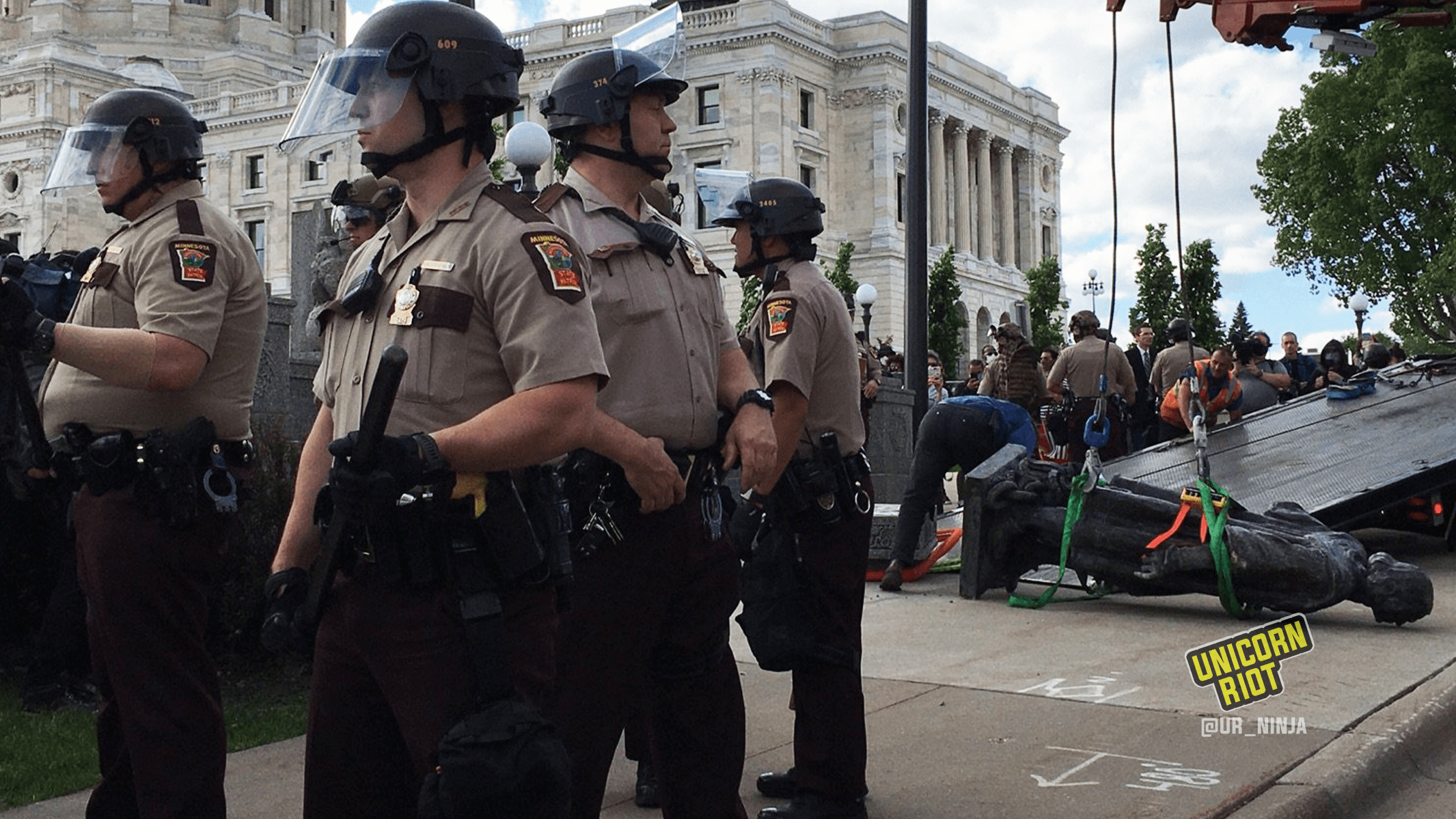 image: state troopers with weapons stand between community members and the statue of Christopher Columbus which was toppled from its pedestal on the grounds of the Minnesota State Capitol on June 10, 2020. The statue is face-down on the ground. Straps are wrapped around the statue – it is about to be hoisted into the air and then placed on a flat-bed truck for removal.
