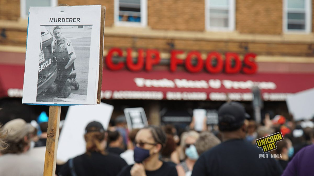 image: hundreds of protesters stand at the intersection of 38th & Chicago in Minneapolis. Everyone is wearing a cloth or paper face mask. In the background is the store front CUP FOODS, in the foreground is a sign with a black-and-white photograph of Derek Chauvin kneeling on the neck of George Floyd in front of the police vehicle; a screenshot from the viral video that shows Floyd's death. The word MURDERER is written above the photograph.