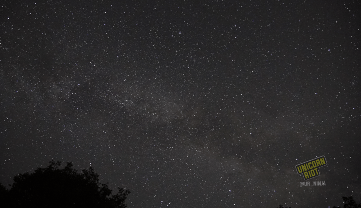 image: ten-second long exposure shot of the night sky facing East, in the northern hemisphere at midsummer. The nebulous arm of our spiral galaxy The Milky Way is visible stretching across the night sky from right to left in the image.