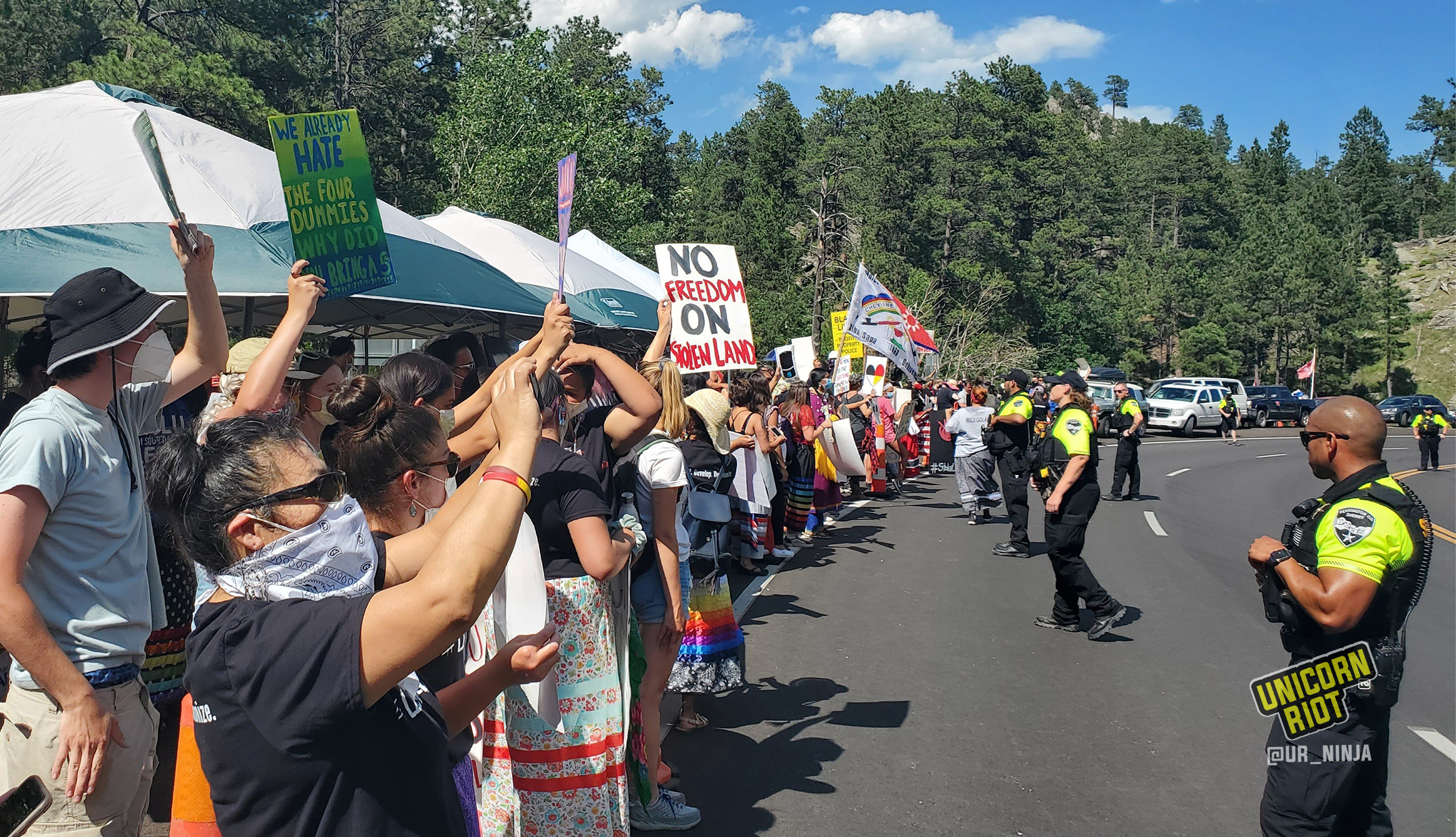 "image: Indigenous people and activists gathered on the side of the road leading to Keystone, SD. The anti-Trump, anti-Mount Rushmore demonstrators hold protests signs such as ""We already hate the four dummies, why did you bring a 5th?"""