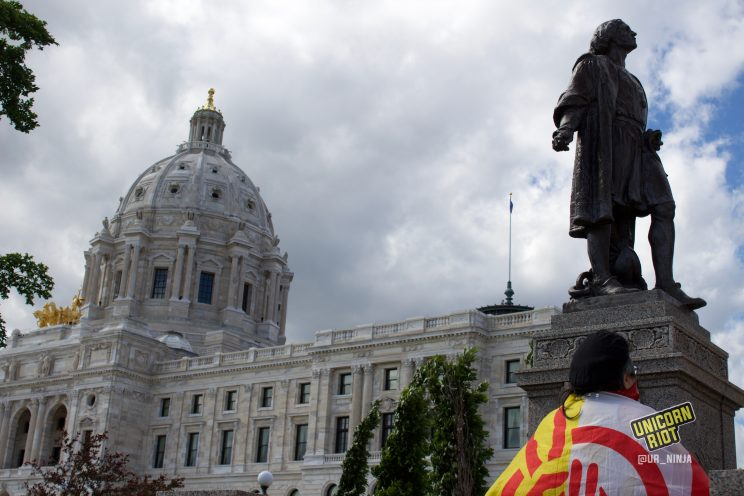 Man with American Indian Movement flag drapped across his back looks at Columbus statue before it got taken down