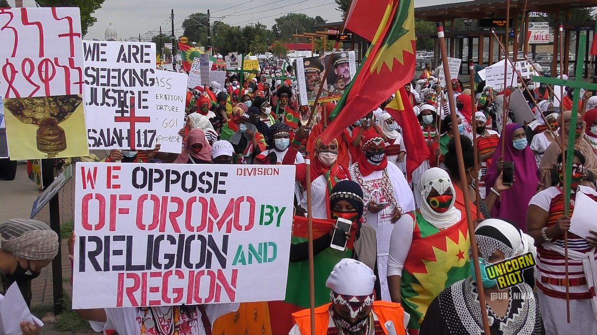 "Sign reads ""We oppose division of Oromo by religion and region"" at the women's march on August 7, 2020 in Saint Paul, MN"