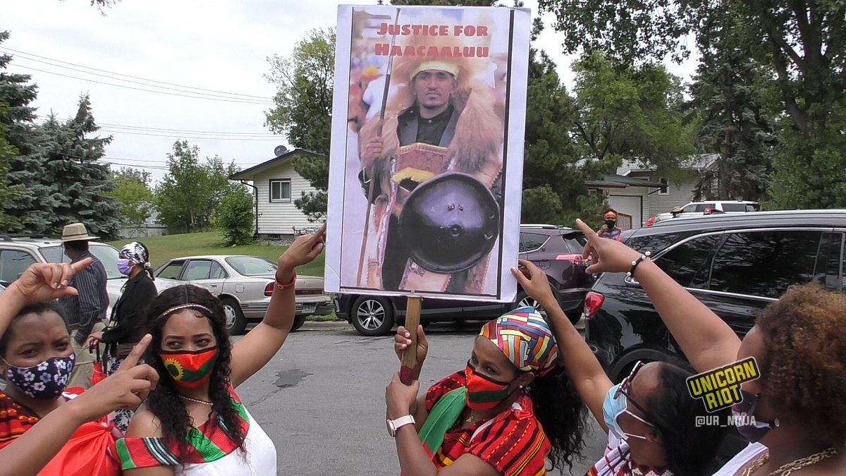 Oromo women point to a poster of Hachalu Hundessa before the August 7 Women's March