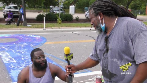 Charles Caldwell passes the mic to his son Charles after painting the R* in Black Lives Matter mural in Minneapolis