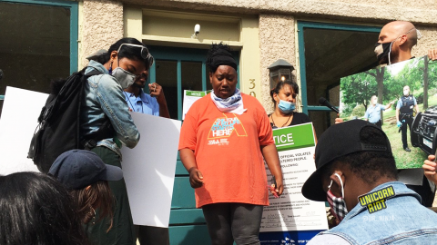 image: a Black woman in an orange shirt is adding tape to a piece of paper, a list of demands for the Minneapolis Parks & Recreation Board Superintendent, Al Bangoura. On the woman's left is a Lakota man with chest-length black hair, as well as a media-maker with their back turned. On the right is a member of Minneapolis Parks & Power; he is wearing a mask and holding a blown-up photograph from when Minneapolis Police assisted in the violent clearing of the sanctuary encampment at Powderhorn Park on Friday, August 14, 2020.