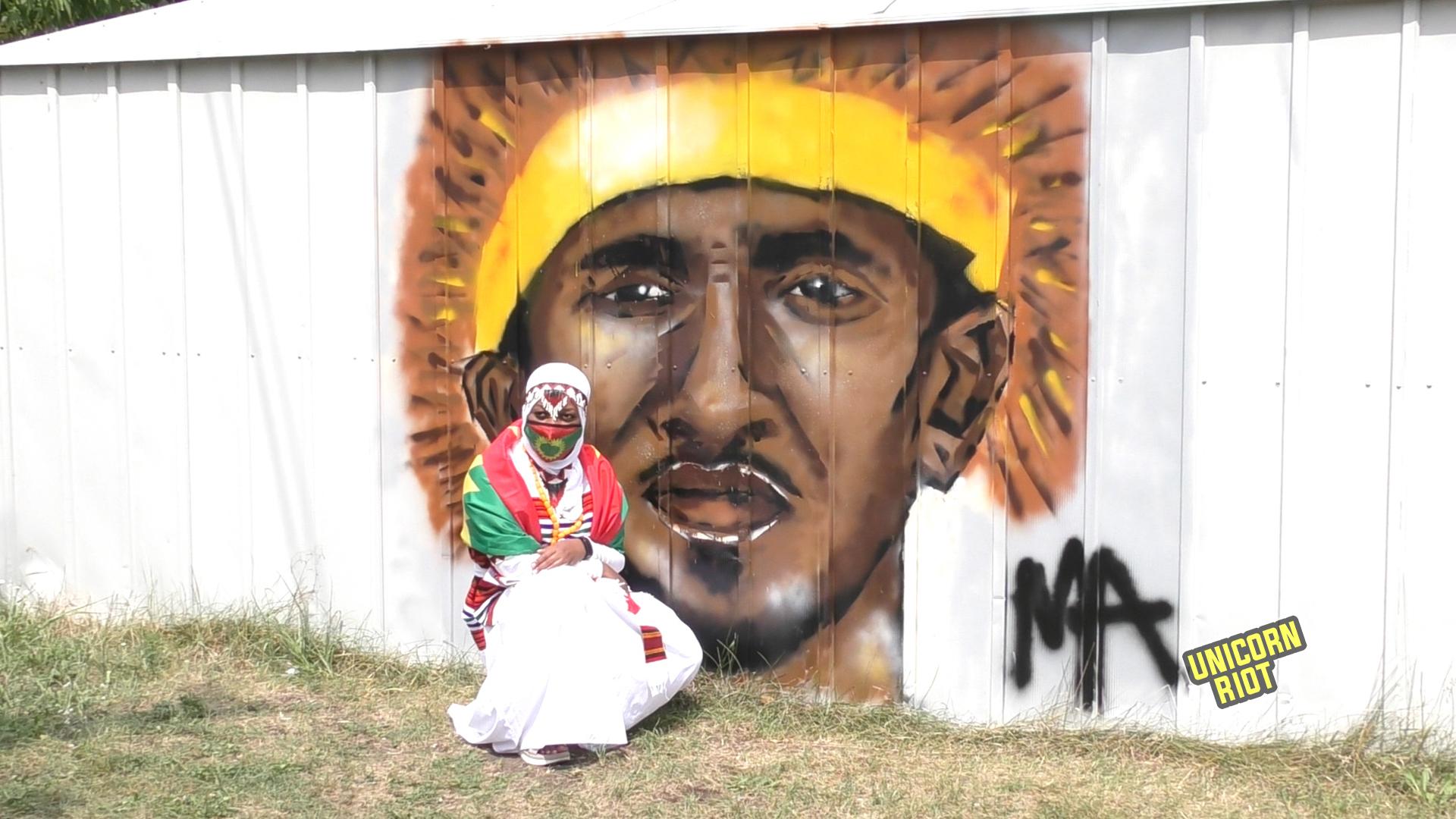 Oromo woman kneels next to mural of Hanchalu Hundessa on the back of the Minnesota Oromo Community Center