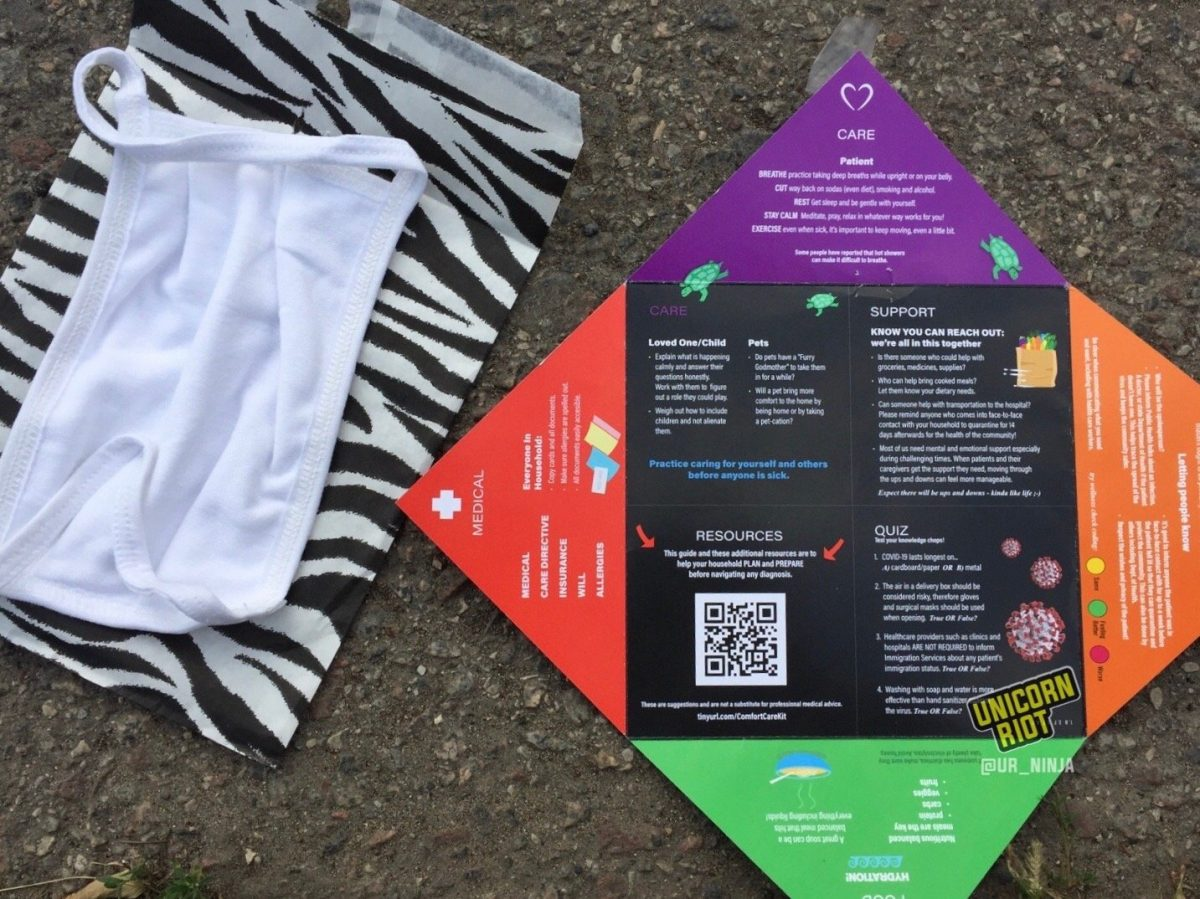 image: a white cloth mask rests atop a white paper envelope printed with black zebra print stripes. Beside this is a handout with information about preventing coronavirus infection, and what to do if/when one has contracted the virus.