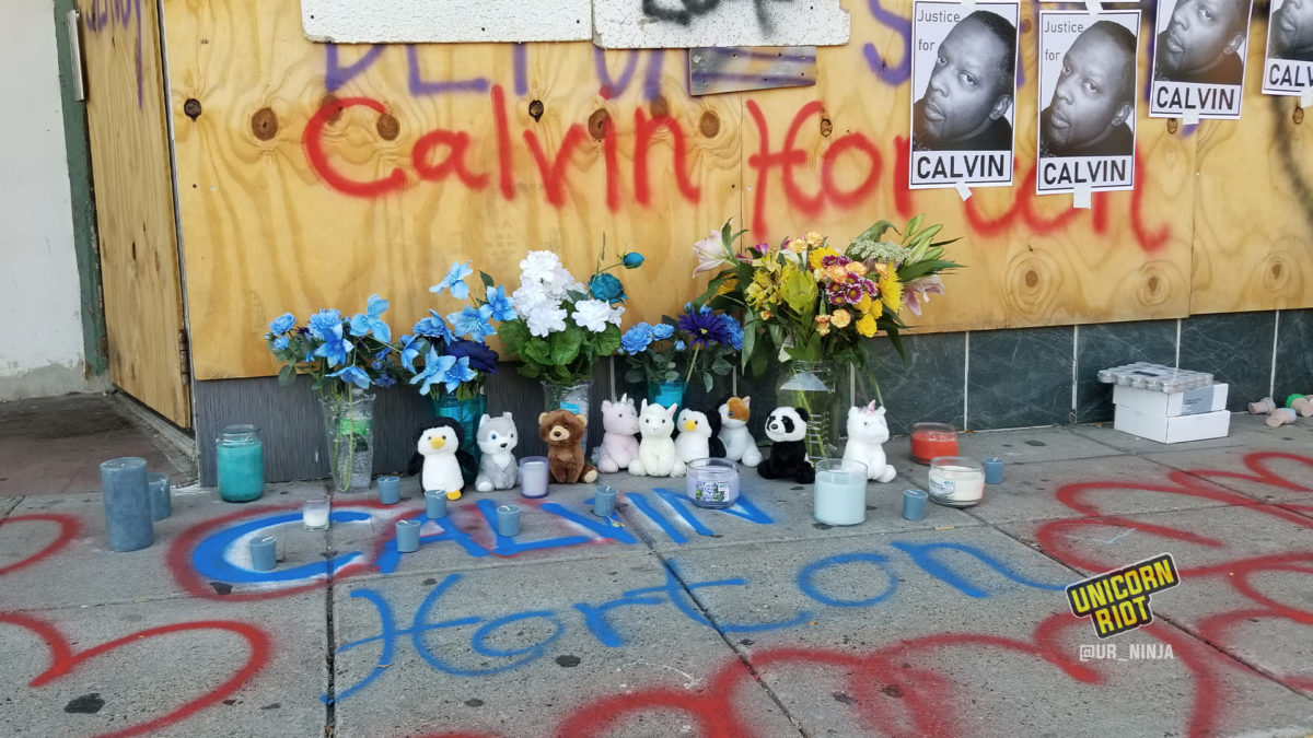 Candles mark where Calvin Horton lay after he was shot