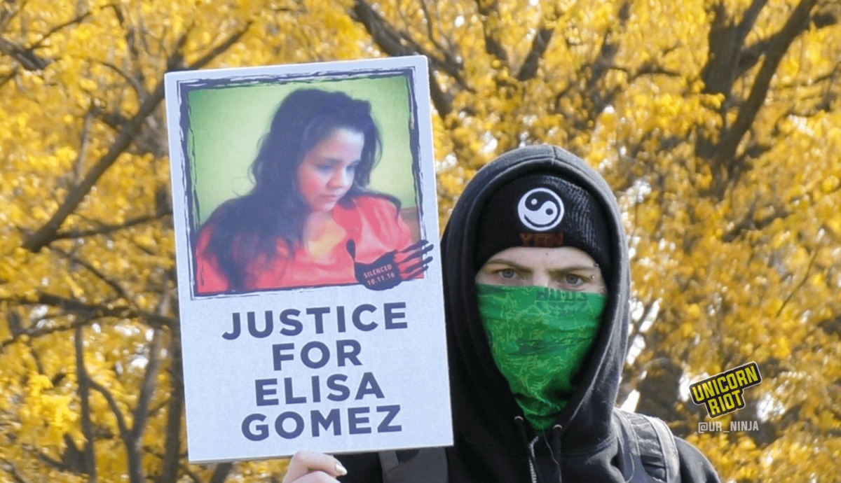 "image: Masked protester holds ""Justice For Elisa Gomez"" protest sign. The sign has a picture of Elisa Gomez with long dark hair and an orange blouse, looking down and to the right. It also has an image of a black handprint with ""Silenced 10.11.16"" white text overlaid. The protester is wearing a black hooded sweatshirt with the hood up, as well as a black knit cap with a black-and-white Yin Yang symbol, and a green cloth face scarf. They are staring directly into the camera; they have light-colored eyes and white skin, and shiny polish on their nails. Behind them out of focus is a canopy of tree leaves, all turned yellow because of the autumn season."