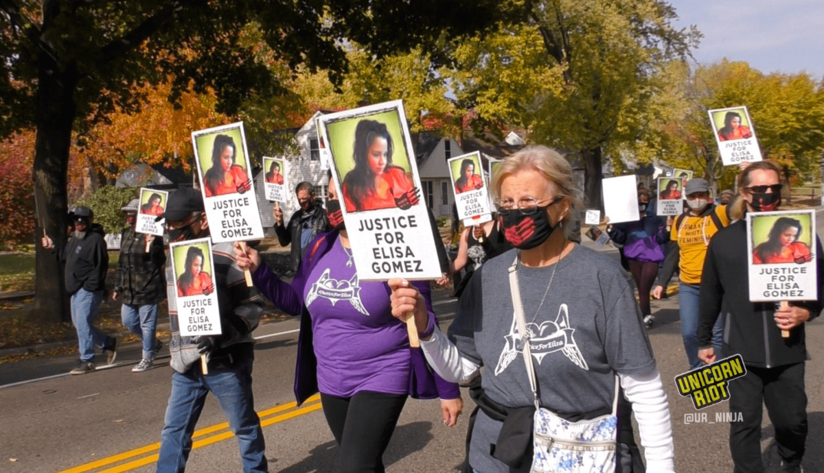 "image: Masked protesters hold ""Justice For Elisa Gomez"" protest signs. Each sign has a picture of Elisa Gomez with long dark hair and an orange blouse, looking down and to the right. It also has an image of a black handprint with ""Silenced 10.11.16"" white text overlaid. More than a dozen protesters are pictured, many wearing black cloth face masks with a red handprint on the front."