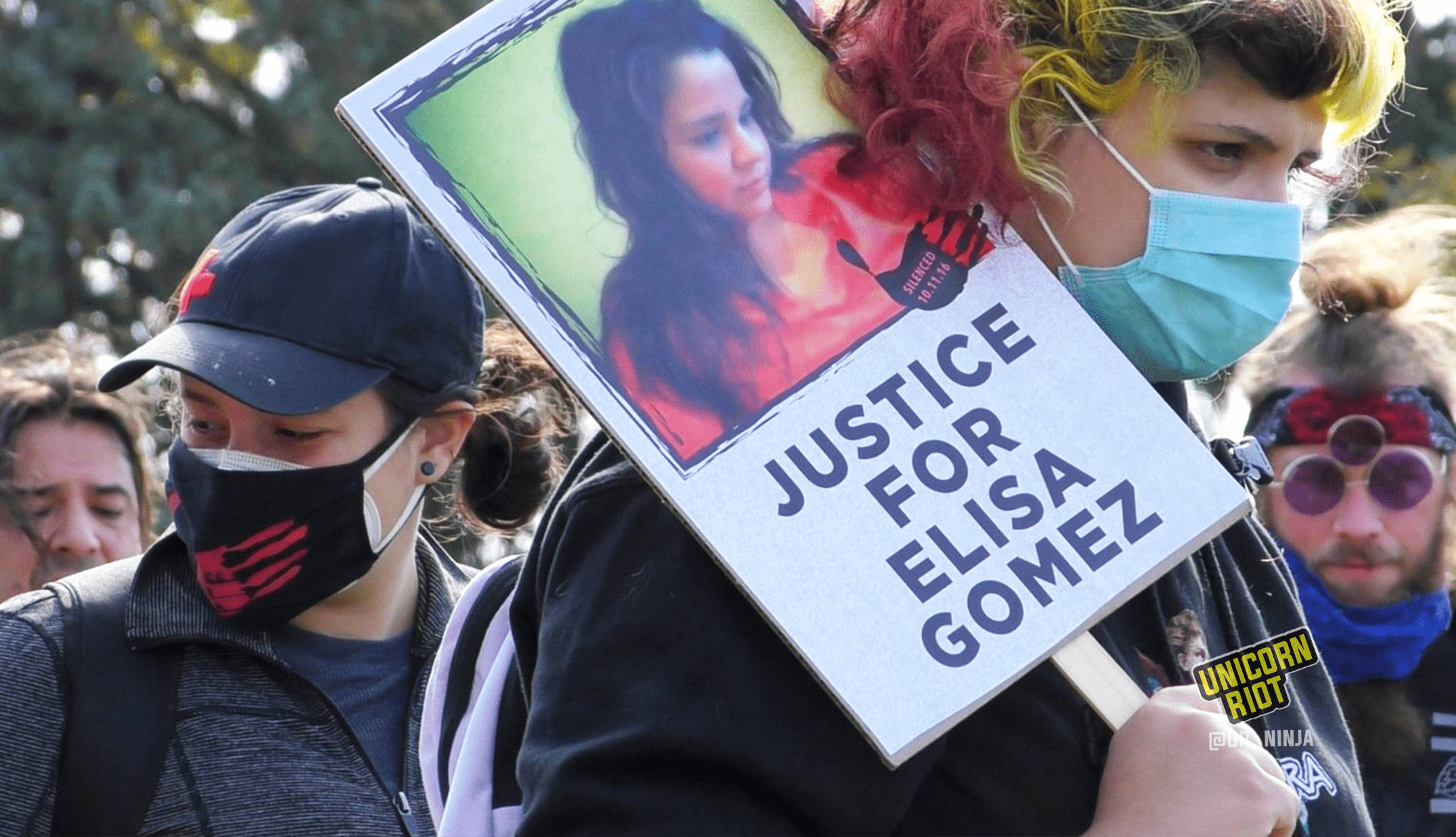 "image: Masked protester holds ""Justice For Elisa Gomez"" protest sign. The sign has a picture of Elisa Gomez with long dark hair and an orange blouse, looking down and to the right. It also has an image of a black handprint with ""Silenced 10.11.16"" white text overlaid. The protester has on a blue medical facemask, is wearing a black sweatshirt and a purple backpack, and has shoulder-length slightly-curled hair that is dyed yellow and pink. They are looking to the right. Several other masked protesters are behind this person."