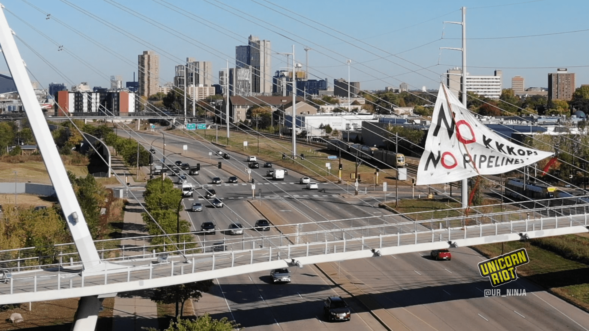 "image: a white triangular banner hangs from the cables above the suspension bridge over Hiawatha Avenue in Minneapolis, oriented towards the right. ""NO KKKOPS, NO PIPELINES"" is written in mostly-black text; in both of the NOs, the letter O is in red. Red ""DANGER"" caution-type plastic tape is attached at the top point of the triangle and at the point on the right. The city skyline is visible behind the bridge, and there are cars on Highway 55/Hiawatha Avenue below the pedestrian bridge."