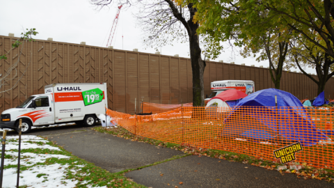 image: the perimeter of a sanctuary tent camp area is surrounded by orange plastic construction fencing; the fence cuts diagonally across the image from bottom right, to the left of the image. On the sidewalk outside of the fencing, two U-Haul trucks are parked; residents' belongings are inside, being moved from MLK Park to another location. A gray tent with a blue tarp is propped up beneath and to the left behind the trunk of a maple tree. To the right of the tree is a waste bin that says City of Minneapolis on its side. Partially-melted snow is visible on the ground.