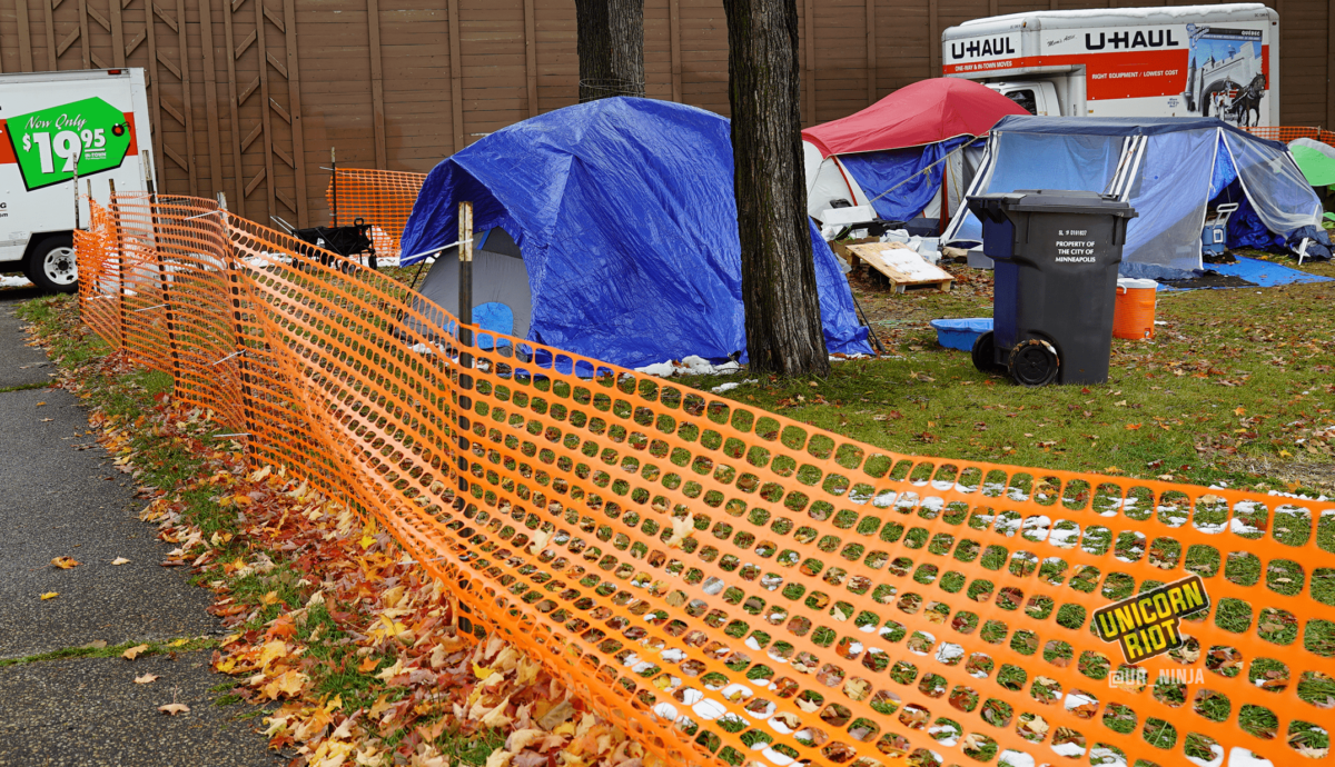 image: the perimeter of a sanctuary tent camp area is surrounded by orange plastic construction fencing; the fence cuts diagonally across the image from bottom right, to the left of the image. On the sidewalk outside of the fencing, two U-Haul trucks are parked; residents' belongings are inside, being moved from MLK Park to another location. A gray tent with a blue tarp is propped up beneath and to the left behind the trunk of a maple tree. To the right of the tree is a waste bin that says Property Of the City of Minneapolis on its side. Other tents are visible in the background.