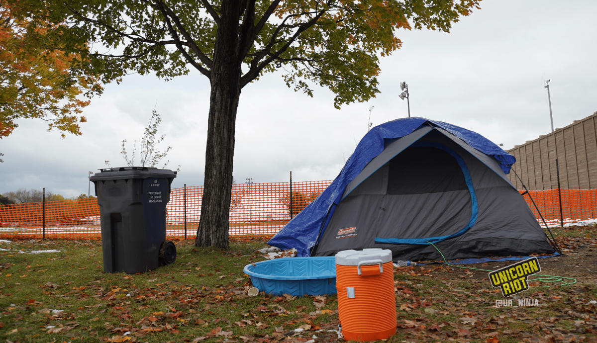 image: a blue and gray tent is propped up beneath and to the right of a maple tree, whose leaves are changing from lime green to yellow, orange, and red tones.  In front of the tent is a children's blue plastic swimming pool, and in front of the pool is an orange water cooler. To the left of the tree is a waste bin that says City of Minneapolis on its side. The entire site is surrounded by orange plastic construction fencing.