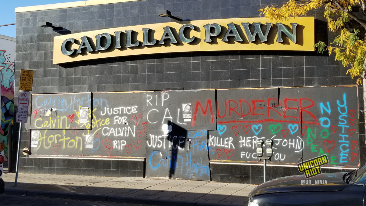 boarded up windows at Cadillac Pawn are spray painted with Justice for Calvin Horton and