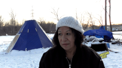 image: Brenda a 60-year-old Native American woman speaks in the center of the frame. She is wearing a white knit hat and a black zip-up jacket. Behind her on the ground is white snow, and to her left in the background is an Indigenous structure known as a Tarpee, a tipi-like structure made with tarps constructed to help elders keep warm while fighting oil pipeline extraction on Native land.