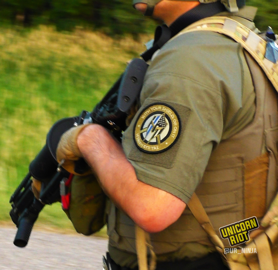 "a responding officer with a blue line patch that says ""with your shield, or not"""